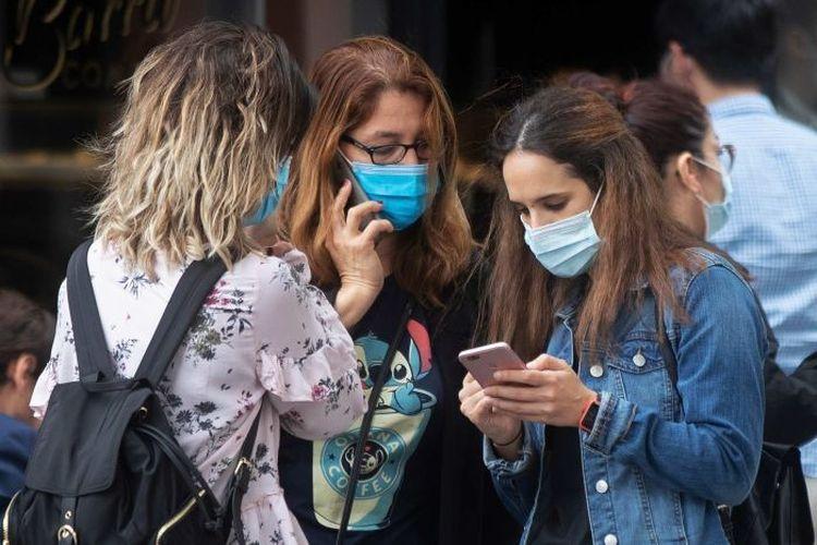 Tiga perempuan memakai masker untuk membantu mencegah penyebaran virus corona di Madrid, Spanyol, pada Kamis, 8 Oktober 2020.