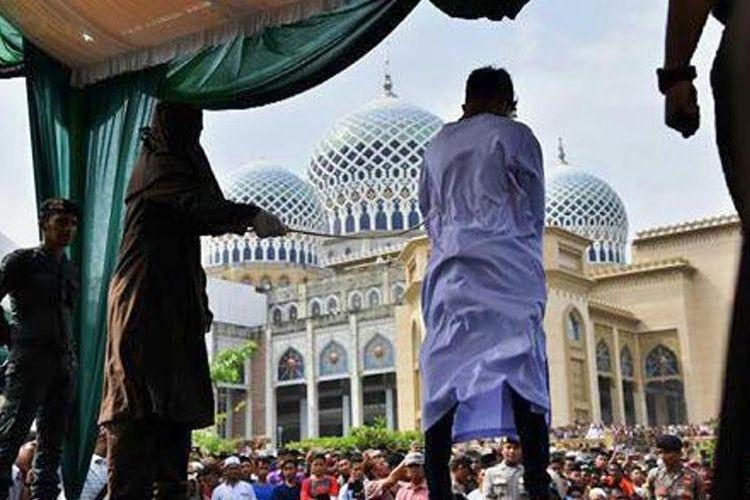 Seorang terhukum cambuk menjalani eksekusi cambuk di halaman Masjid Islamic Center, Kota Lhokseumawe, Jumat (23/3/2018).