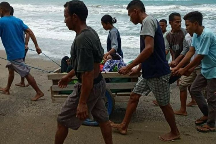 Puluhan warga Desa Desa Misinh, Kecamatan Kilmuri, Kabupaten Seram Bagian Timur membawa seorang warga yang sakit dengan gerobak menuju puskesmas di Kilmuri, Minggu (21/2/2021)