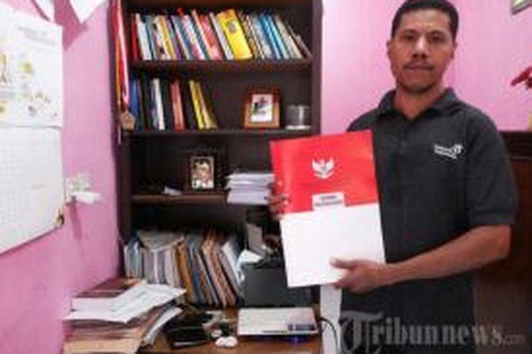 Marten Boiliu menunjukkan putusan uji materiil Pasal 96 UU Ketenagakerjaan yang permohonannya dikabulkan oleh Mahkamah Konstitusi, di kediamannya, di Jalan Wibawa Mukti RT 01/18 Nomor 137, Kelurahan Jatimekar, Kecamatan Jatiasih, Kota Bekasi, Sabtu (21/9/2013). Marten yang berprofesi sebagai kepala satpam ini seorang diri mengajukan permohonan uji materiil Pasal 96 UU Ketenagakerjaan ke MK dan ternyata permohonannya dikabulkan.