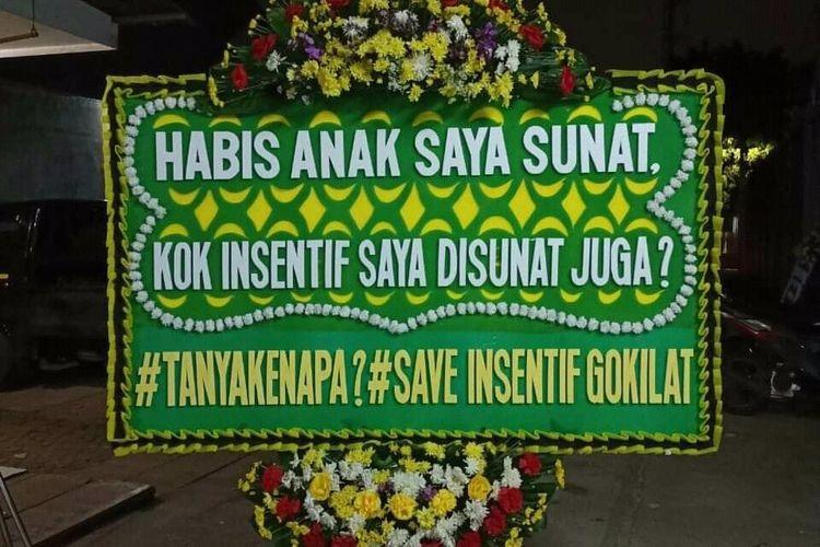 Mitra Mitra Gojek untuk layanan GoSend Same Day atau GoKilat mengirimkan karangan bunga sebagai bentuk aksi protes terkait perubahan skema insentif ke kantor Gojek di Jalan Kemang Timur, Bangka, Mampang Prapatan, Jakarta Selatan pada Selasa (8/6/2021).