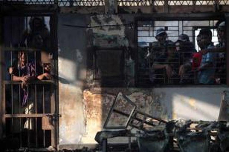 Narapidana berada di balik jeruji tahanan dengan bangunan yang terbakar di Lembaga Pemasyarakatan (Lapas) Klas I Tanjung Gusta, Medan, 12 Juli 2013.  Lapas dibakar narapidana pada 11 Juli. Dua petugas dan tiga narapidana tewas serta 150 narapidana kabur, termasuk narapidana teroris.