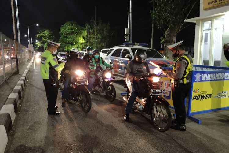 Jajaran Kepolisian Polres Pelabuhan Tanjung Perak dan Tim Gabungan Lainnya Saat Melakukan Pemeriksaan Kendaraan Pribadi yang Akan Melintasi Jembatan Suramadu dan Masuk Ke Madura, Kamis (6/5/2021).