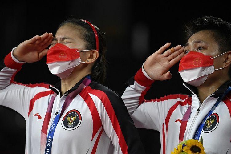 Pasangan ganda putri Indonesia Greysia Polii dan Apriyani Rahayu (kanan) memberi hormat dengan medali emas bulu tangkis ganda putri pada upacara Olimpiade Tokyo 2020 di Musashino Forest Sports Plaza di Tokyo pada 2 Agustus 2021.