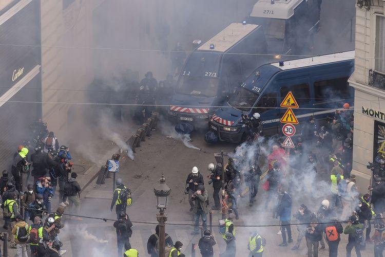 Polisi anti huru-hara Perancis memblokade para anggota massa gilets jaunes (Rompi Kuning) dengan gas air mata terlihat di Champs-Elysees, Paris, Perancis, pada 8 Desember 2018.