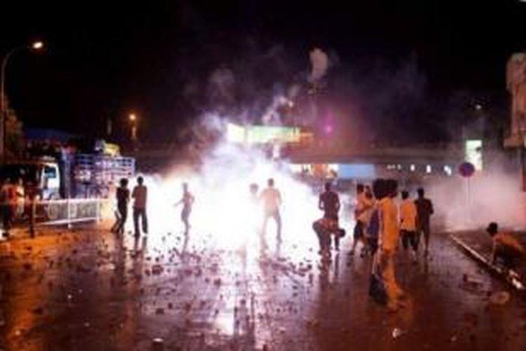 Demonstran bentrok dengan polisi di Phnom Penh, Kamboja, Minggu (15/9/2013).