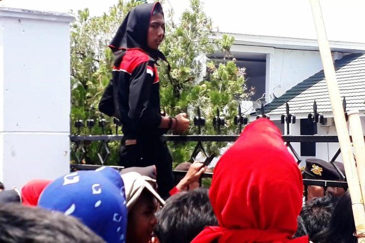 Pengunjuk rasa yang dilarang masuk ke dalam Gedung DPRD Palopo hanya bisa berteriak menyuarakan tuntutannya dengan memanjat pagar, Senin (28/10/2019).