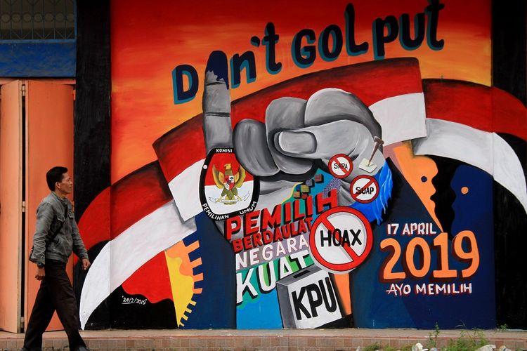 Warga melintas di depan mural tentang pemilu 2019 di Pasar baru Mamuju, Sulawesi Barat, Rabu (6/03/2019). Mural tersebut mengangkat tema mengajak warga untuk mensukseskan pemilu pada 17 April 2019 dengan berpartisipasi dan tidak Golput. ANTARA FOTO/ Akbar Tado/hp.