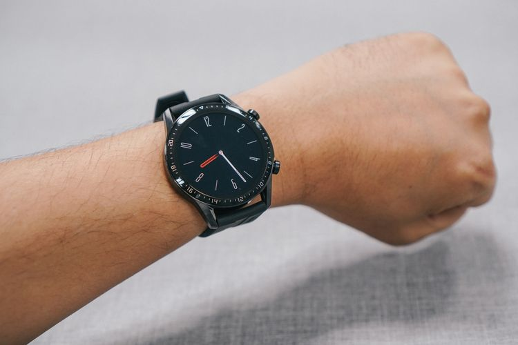 Huawei Watch GT 2 di pergelangan tangan. Jam di layar merupakan tampilan always-on display yang lebih sederhana dibanding watch face utama.