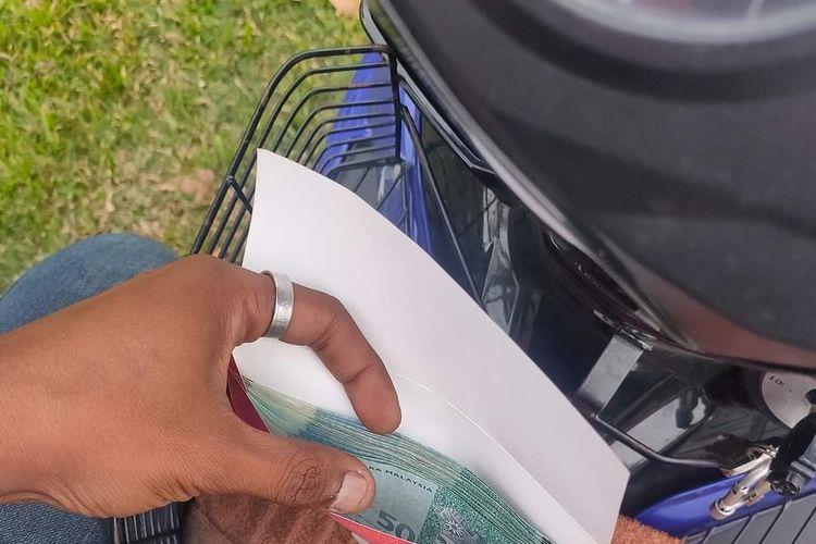 Amplop berisi uang 1.000 ringgit (Rp 3,5 juta) yang didapat driver FoodPanda M Faris Faizul, setelah mengantar makanan. Pemesan meminta ia didoakan cepat punya anak.