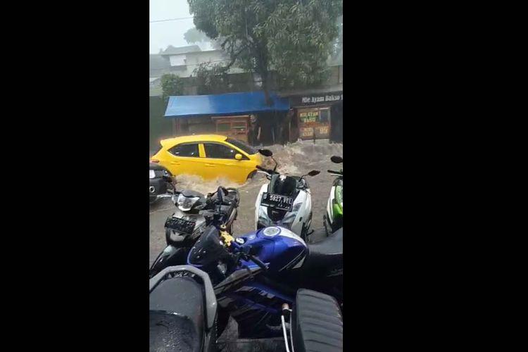 Sebuah mobil tampak terseret banjir yang menerjang Kota Bandung, Kamis (24/12/2020).