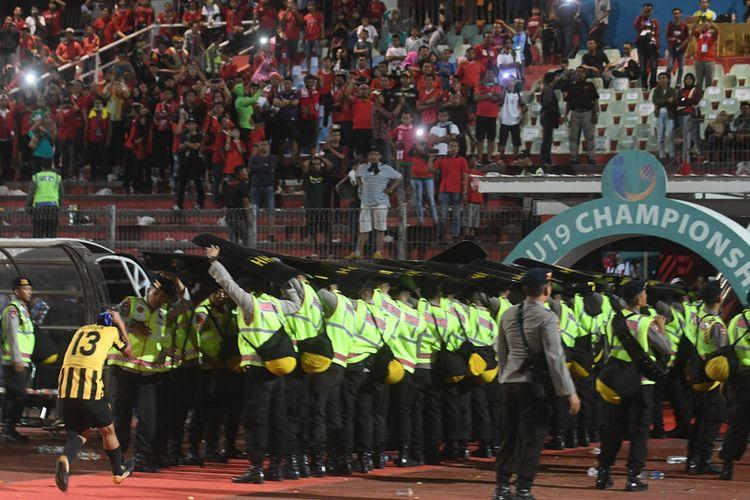 Petugas keamanan berusaha melindungi pesepak bola  Malaysia U-19 Mohamad Izzuddin (kiri) dari lemparan suporter Indonesia usai laga semifinal Piala AFF U-19 di Gelora Delta Sidoarjo, Sidoarjo, Jawa Timur, Kamis (12/7/2018). Indonesia kalah adu penalti dari Malaysia dengan skor 3-4.