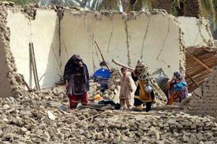 Sebuah keluarga di distrik Awaran berjalan melintasi sebuah rumah yang sudah hancur akibat gempa bumi berkekuatan 7,7 SR yang mengguncang kawasan itu. Gempa ini sudah menewaskan lebih dari 300 orang.