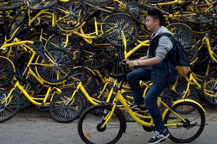 Seorang pria bersepeda melewati tumpukan di Beijing, China. (Sky News)