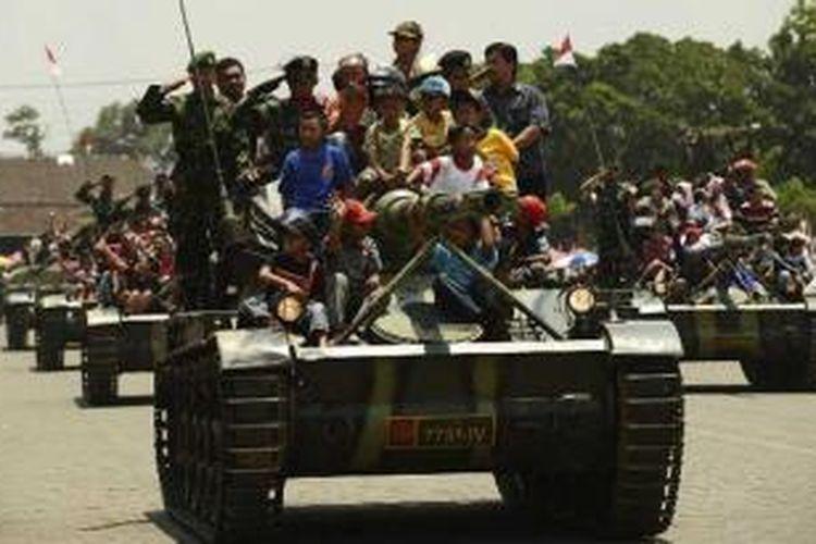 Warga mengikuti defile pasukan dengan menaiki tank saat peringatan HUT ke-67 Tentara Nasional Indonesia di lapangan Jenderal Soedirman, Ambarawa, Kabupaten Semarang, Jawa Tengah, Jumat (5/10/2012).