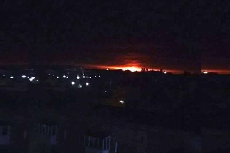 Cahaya terlihat dari sebuah gudang senjata di Ichnia, Ukraina, yang dilaporkan meledak dan terbakar Selasa dini hari (9/10/2018).