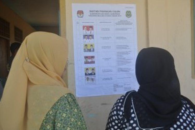 Warga Maluku Utara melihat gambar para pasangan calon Gubernur dan Wakil Gubernur Maluku Utara periode 2013-2018, di Tempat Pemungutan Suara (TPS), Senin (1/7/2013).