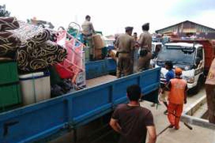 Warga Bukit Duri, Jakarta Selatan yang direlokasi saat tiba di Rusun Rawa Bebek, Cakung, Jakarta Timur menumpang truk Satpol PP dan Dinas Kebersihan DKI. Minggu (14/8/2016)
