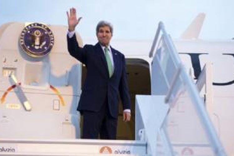 Menteri Luar Negeri John Kerry melambaikan tangan sebelum memasuki pesawat di bandar udara Orly, Paris selatan (15/10).