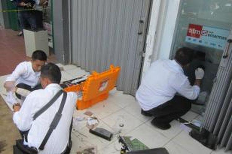 Polisi sedang melakukan olah tempat kejadian perkara di ATM Sinar Mas yang dirampok sehingga bank tersebut mengalami kerugian hingga Rp 80 juta