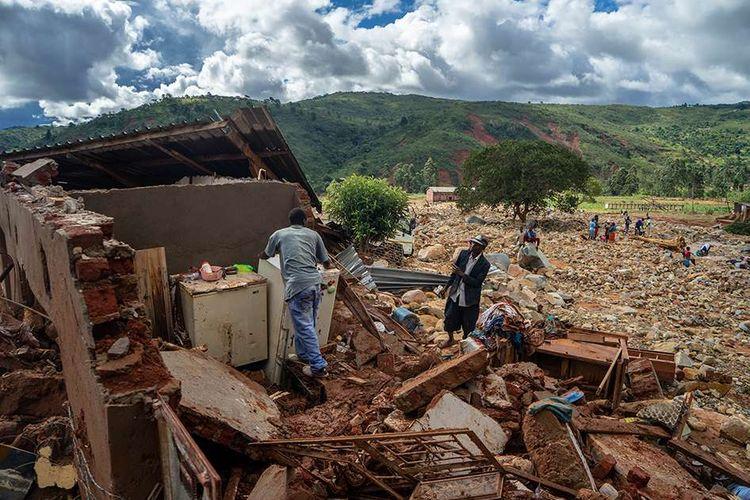 Seorang pria di tengah rumah yang hancur akibat terjangan topan Idai di Chimanimani, Zimbabwe, Selasa (19/3/2019). Ratusan orang tewas dan lainnya hilang di Mozambik dan Zimbabwe setelah topan Idai membawa serta banjir bandang dan angin kencang, 17 Maret lalu.