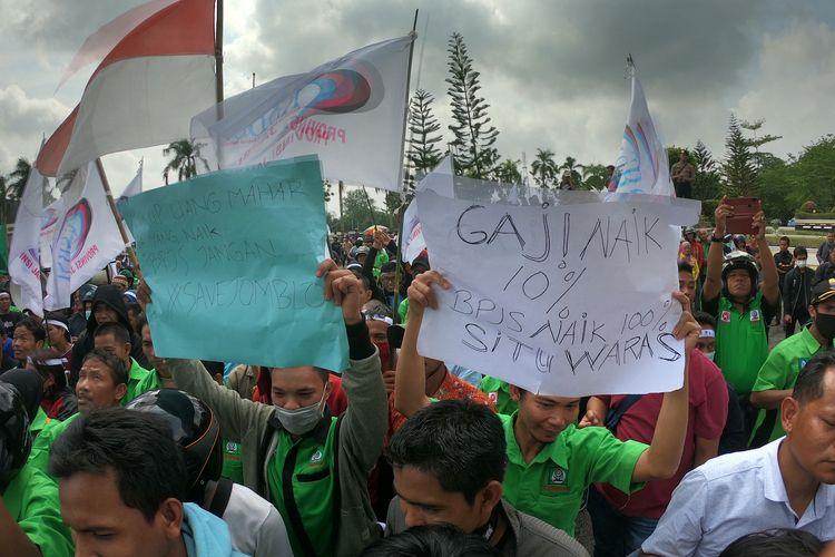 Massa Konfederasi Serikat Buruh Sejahtera Indonesia (KSBSI) membawa poster berisi tuntutan saat unjuk rasa tarif BPJS Kesehatan di Kantor DPRD Provinsi Jambi, Jambi, Senin (30/9/2019). Aksi massa tersebut menolak kebijakan pemerintah yang berencana menaikkan tarif BPJS Kesehatan dan mendesak perbaikan menyeluruh terhadap sistem pelayananan dan pengelolaan jaminan kesehatan warga. ANTARA FOTO/Wahdi Septiawan/ama.