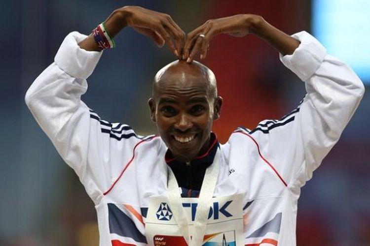 Pelari Inggris Mo Farah dengan gaya khasnya di atas podium usai pengalungan medali emas setelah dia memenangkan final nomor 10.000 meter dalam kejuaraan dunia atletik 2013 di Moskwa, Rusia.