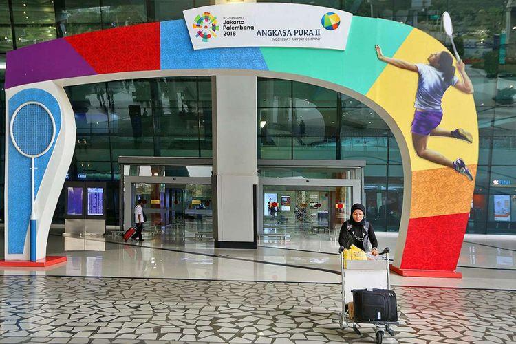 Seorang penumpang melintas di sekitar gapura bertuliskan Asian Games 2018  yang ada di Terminal 3 Keberangkatan Bandara SOekarno-Hatta, Tangerang, Banten, Kamis (5/07/2018). PT Angkasa Pura AP (II) selaku pengelola bandara menyatakan siap memfasilitasi kedatangan dan kepulangan peserta Asian Games 2018 dengan menyiapkan sarana dan prasarana di tiga bandara yakni Bandara Soekarno Hatta, Bandara Sultan Mahmud Badaruddin II Palembang dan Husein Sastranegara Bandung.