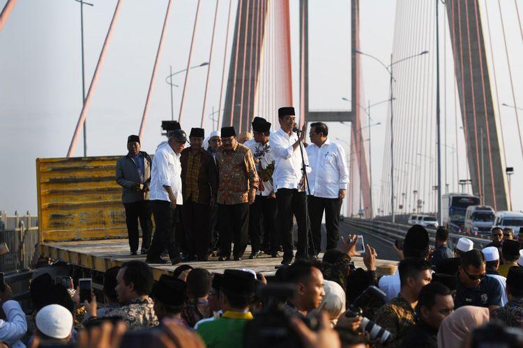 Presiden Joko Widodo (kedua kanan) didampingi Menteri PUPR Basuki Hadimuljono (kedua kiri) dan Sekretaris Kabinet Pramono Anung (kanan) serta pejabat setempat dan para ulama berada diatas truk saat meresmikan pembebasan tarif tol Jembatan Suramadu di Surabaya, Jawa Timur, Sabtu (27/10/2018). Pembebasan tarif tol tersebut diharapkan berdampak pada pertumbuhan ekonomi di Pulau Madura.