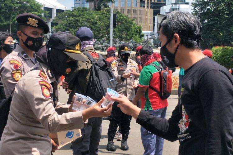Sejumlah polisi membagikan air minum kepada para buruh yang menggelar aksi demonstrasi di depan di sekitar Bundaran Patung Kuda Arjuna Wijaya, Senin (12/4/2021).