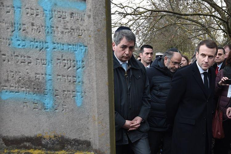 Presiden Perancis Emmanuel Macron melihat pemakaman yang dirusak dengan simbol swastika di pemakaman Yahudi di Quatzenheim, Selasa (19/2/2019). (AFP/FREDERICK FLORIN)