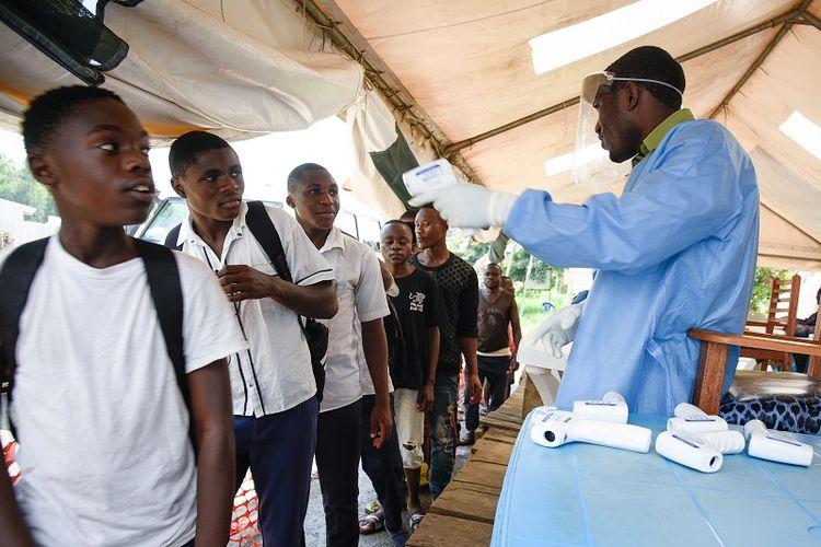 Seorang pekerja kesehatan menggunakan termometer non-kontak untuk memeriksa suhu tubuh warga Republik Demokratik Kongo (RDK) di pusat pemeriksaan Ebola di Mpondwe, Uganda, yang berbatasan dengan DRK.