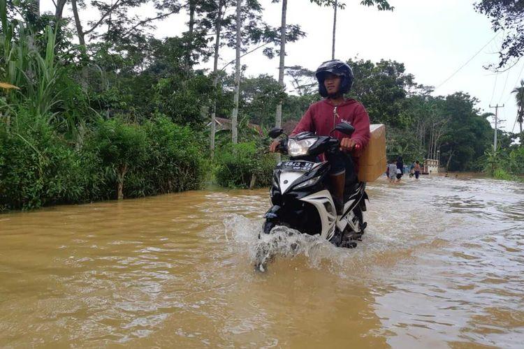 Kendaraan bermotor mencoba melintasi genangan air banjir akibat meluapnya Sungai Citanduy di Desa Tanjungsari, Kecamatan Sukaresik, Kabupaten Tasikmalaya, Minggu (23/2/2020).