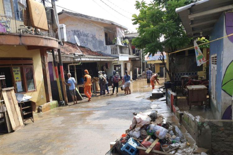 Sejumlah warga dibantu petugas mulai membersihkan sisa-sisa banjir yang sempat merendam sejumlah titik di Kelurahan Rawajati, Pancoran, Jakarta Selatan pada Selasa (9/2/2021) siang.