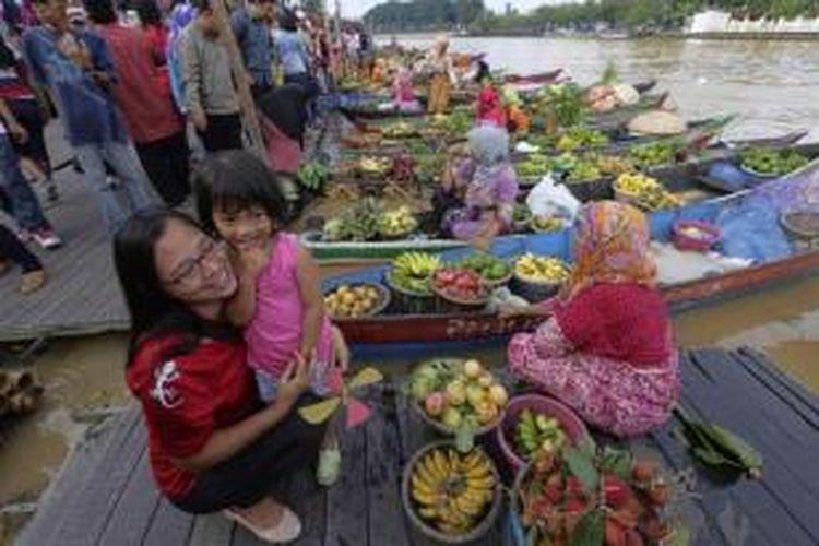 Yayuk dan putrinya Bening, wisatawan asal Kota Bogor, Jawa Barat, mengunjungi pasar terapung di Sungai Martapura di pusat Kota Banjarmasin, Kalimantan Selatan, 23 Maret 2014.