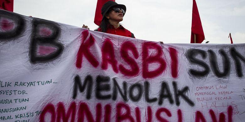 Seorang dari massa yang tergabung dalam Gerakan Buruh Bersama Rakyat (GEBRAK) menggelar aksi penolakan terhadap Omnibus Law RUU Cipta Lapangan Kerja di depan gedung DPR, Jakarta, Senin (13/1/2020). Mereka menolak Omnibus Law RUU Cipta Lapangan Kerja karena akan mempermudah PHK, menghilangkan pesangon, rentan diskriminasi serta penghapusan pidana ketenagakerjaan. ANTARA FOTO/Dhemas Reviyanto/ama.