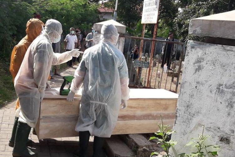 Petugas medis RSUD Kardinah dengan APD lengkap memakamkan seorang pasien Covid-19 yang dimasukan dalam peti di TPU Kelurahan Sumurpanggang, Margadana, Kota Tegal, Rabu (16/9/2020)