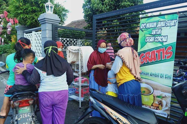 Nampak warga sementara mengambil jamu gratis yang dipercaya berkhasiat mencegah corona di Jalan Sentul, Kelurahan Banjarejo, Kecamatan Taman, Kota Madiun, Jawa Timur, Rabu (15/4/2020).
