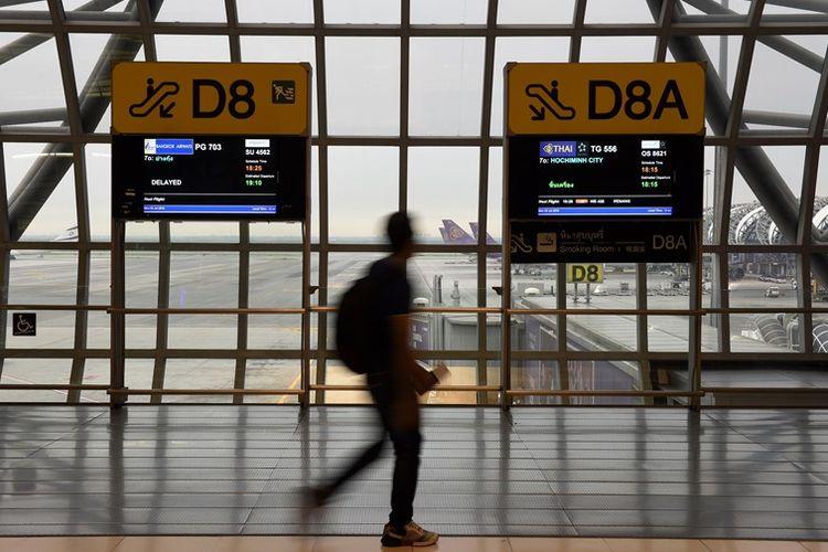 Seorang penumpang melintas di terminal kedatangan di bandara Suvarnabhumi Bangkok, Thailand.