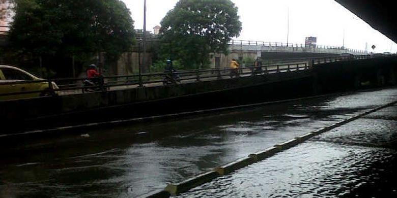Pengendara sepeda motor memasuki pintu tol Sunter untuk menghindari banjir di ruas Jalan Yos Sudarso, Rabu (5/2/2014).