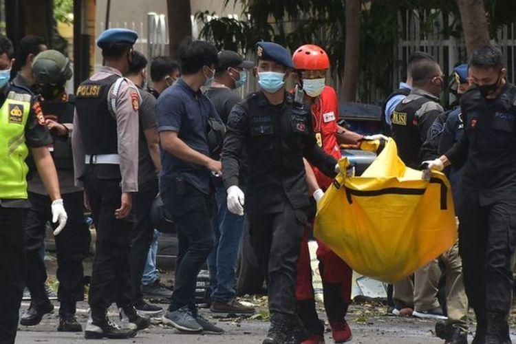 Petugas kepolisian mengangkat kantong jenazah berisi bagian tubuh dari terduga pelaku bom bunuh diri di depan Gereja Katedral Makassar, Sulawesi Selatan, hari Minggu (28/03).