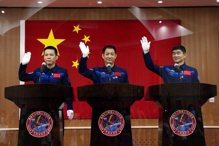 Tiga astronot China (dari kiri) Tang Hongbo, Nie Haisheng, dan Liu Boming melambai saat konferensi pers di Pusat Peluncuran Satelit Jiuquan pada Rabu (16/6/2021). Pada Kamis (17/6/2021), China berencana mengirim tiga astronot tersebut dengan pesawat ulang-alik Shenzhou-12 ke orbit bumi.