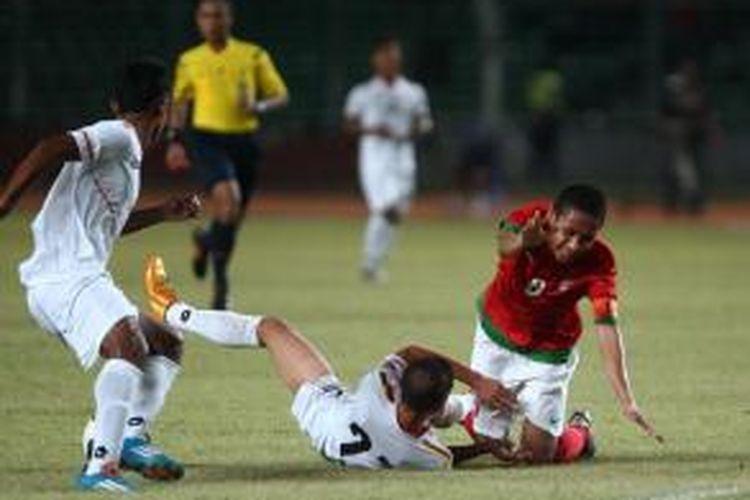 Kapten Timnas U-19 Indonesia Evan Dimas Darmono dihadang pemain U-19 Myanmar, Nan Wai Min dan Htike Htike Aung (kiri) pada pertandingan persahabatan di Stadion Gelora Bung Karno, Jakarta, Senin (5/5).