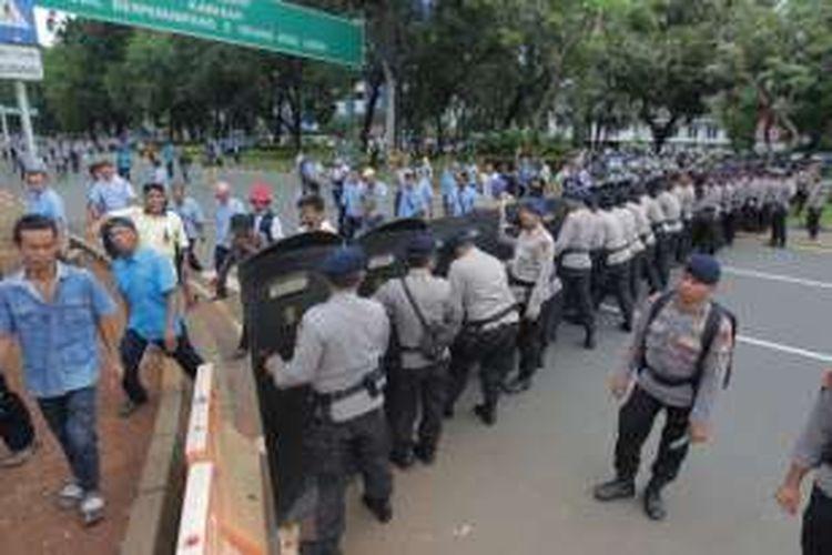 Polisi menjaga keamanan saat sopir taksi melakukan aksi demonstrasi di Jakarta, Selasa (22/3/2016). Mereka menuntut pemerintah menutup angkutan umum berbasis online karena dianggap mematikan mata pencaharian mereka. KOMPAS.com / RODERICK ADRIAN MOZES