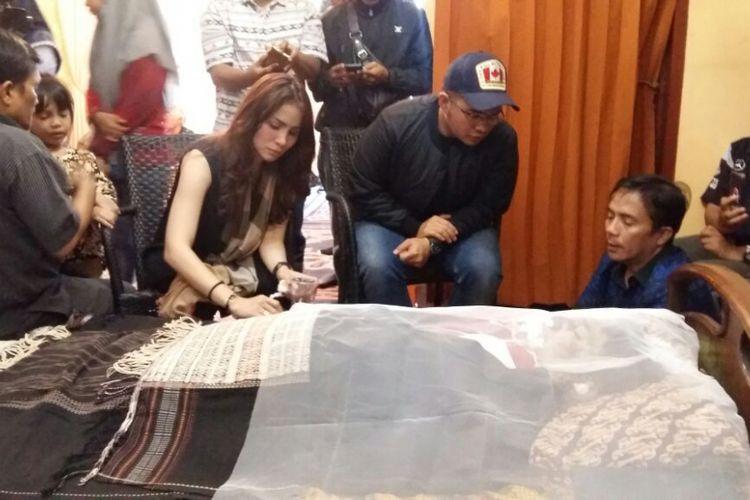 Momo Geisha duduk di samping jenazah ayahnya, Jabonar Sinaga, di Pekanbaru, Riau, Rabu (20/9/2017).