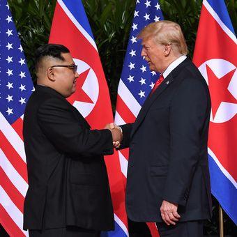 Pemimpin Korea Utara Kim Jong Un (kiri) bersalaman dengan Presiden AS Donald Trump pada pertemuan bersejarah antara AS-Korea Utara, di Hotel Capella di Pulau Sentosa, Singapura, Selasa (12/6/2018). Pertemuan ini merupakan yang pertama kalinya bagi pemimpin kedua negara dan menjadi momentum negosiasi untuk mengakhiri kebuntuan permasalahan nuklir yang telah terjadi puluhan tahun.