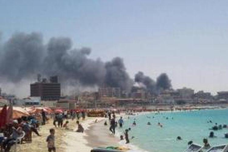Sebuah foto yang disebar lewat akun Twitter seorang fotografer asal Alexandria menampilkan sebagian warga Mesir masih bisa bersantai dan bercengkerama di pantai sementara di latar belakang asap hitam mengepul dari pusat kota Kairo.