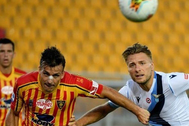 Giulio Donati berebut bola dengan Ciro Immobile dalam laga Lecce vs Lazio pada lanjutan pekan ke-31 Liga Italia yang digelar di Stadion Via del Mare, Rabu (8/7/2020).
