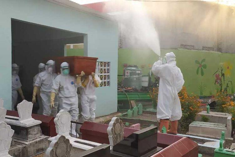 MAKAMKAN—Atong bersama timnya mengubur salah satu jenazah kasus covid-19 di Kota Madiun