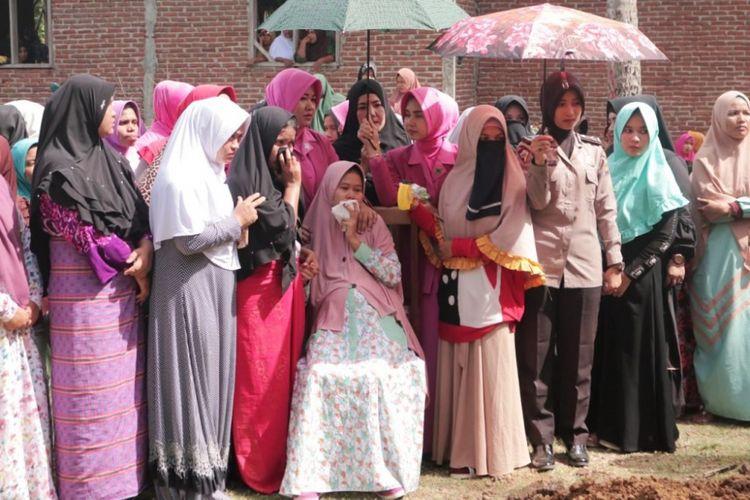 Siti Nur Rahmi (27) tak kuasa menahan tangis saat menyaksikan prosesi pemakaman, jenazah suaminya Bripka Faisal, di Desa Rambong, Kemukiman Beuracan, Kecamatan Meurudue, Kabupaten Pidie Jaya, Minggu (27/8/2018)